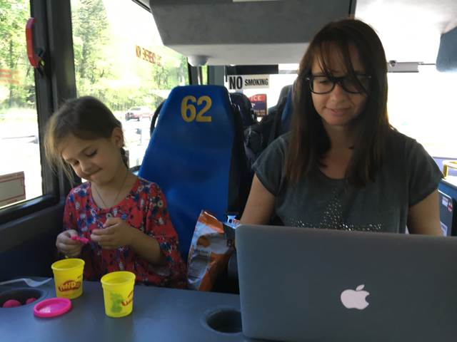 Foto de Vanesa trabajando mientras su hija juega con la plastilina, en un autobús de Washington a Nueva York